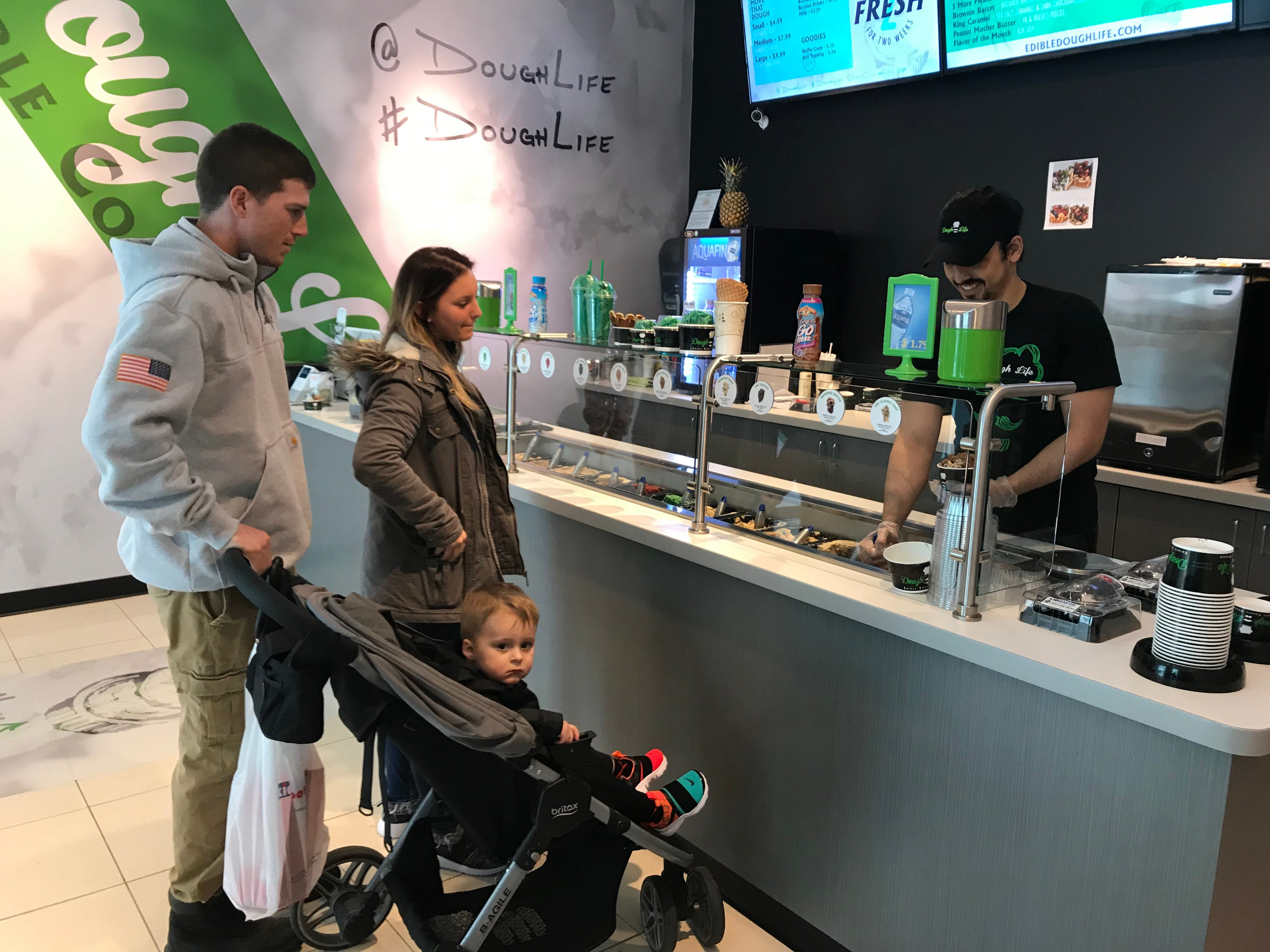 Yasin Cimen, a Dough Life employee, serves Kolin and Julia Sawdey of Hilton, who planned to share their dough with their 2-year-old son, Klayton.
