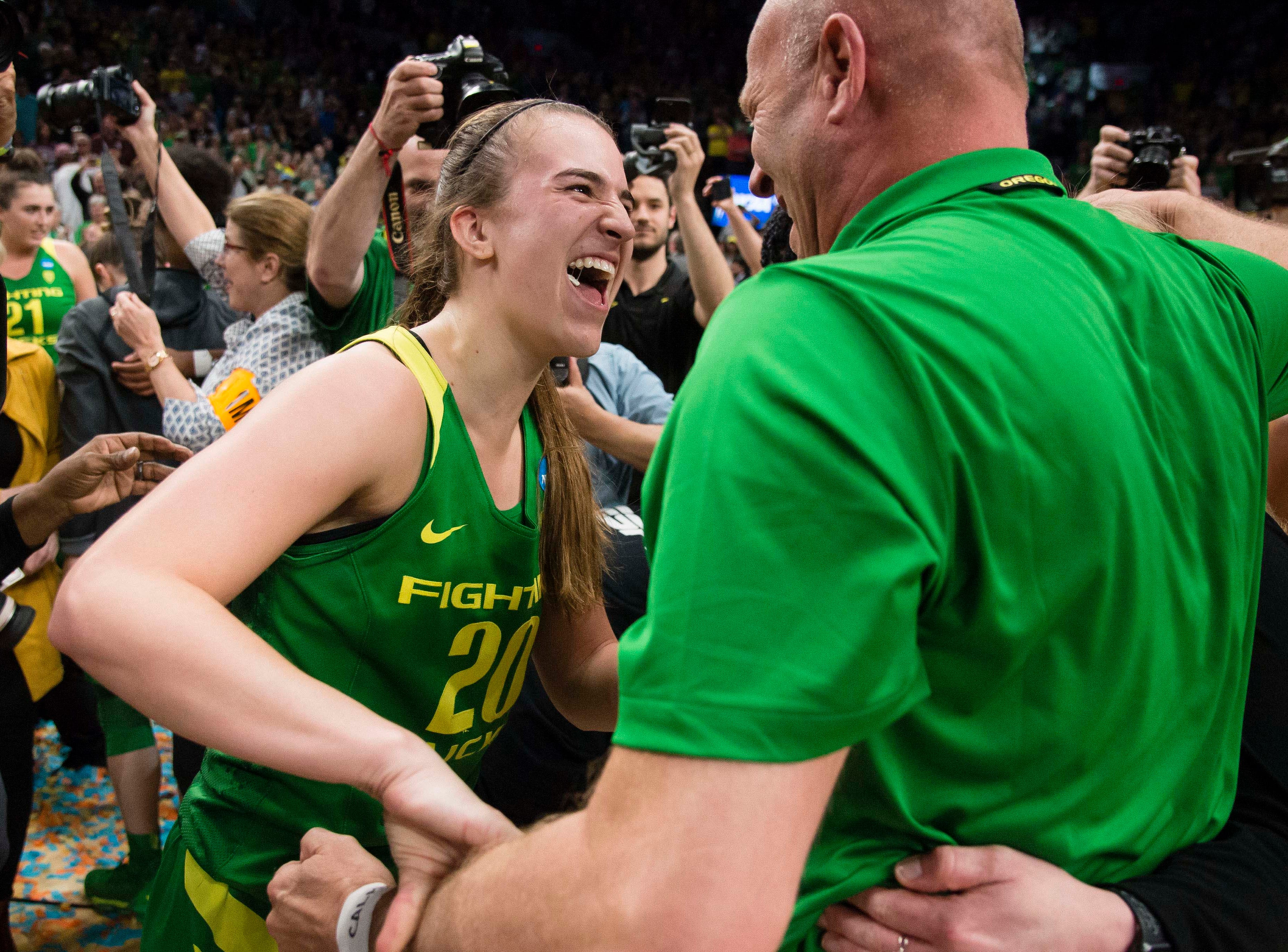 Oregon Ducks guard Sabrina Ionescu (20) celebrates with head coach Kelly Graves after a game against the Mississippi State Bulldogs in the championship game of the Portland regional in the women's 2019 NCAA Tournament at Moda Center. The Oregon Ducks beat the Mississippi State Bulldogs 88-84.
