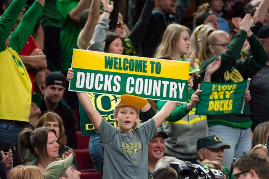 "A young Oregon fan holds up a ""Welcome to Ducks country"" sign, one of many such signs inside the Moda Center when No. 2 seed Oregon defeated No. 1 seed Mississippi State, 88-84, in the Portland Regional Championship Game."