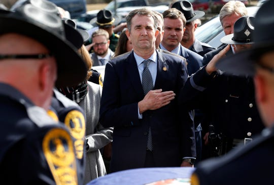 In this Saturday, Feb. 9, file photo, Gov. Ralph Northam, left, and his wife, Pam, watch as the casket of fallen Virginia State Trooper Lucas B. Dowell is carried to a vehicle during his funeral in Chilhowie, Va.
