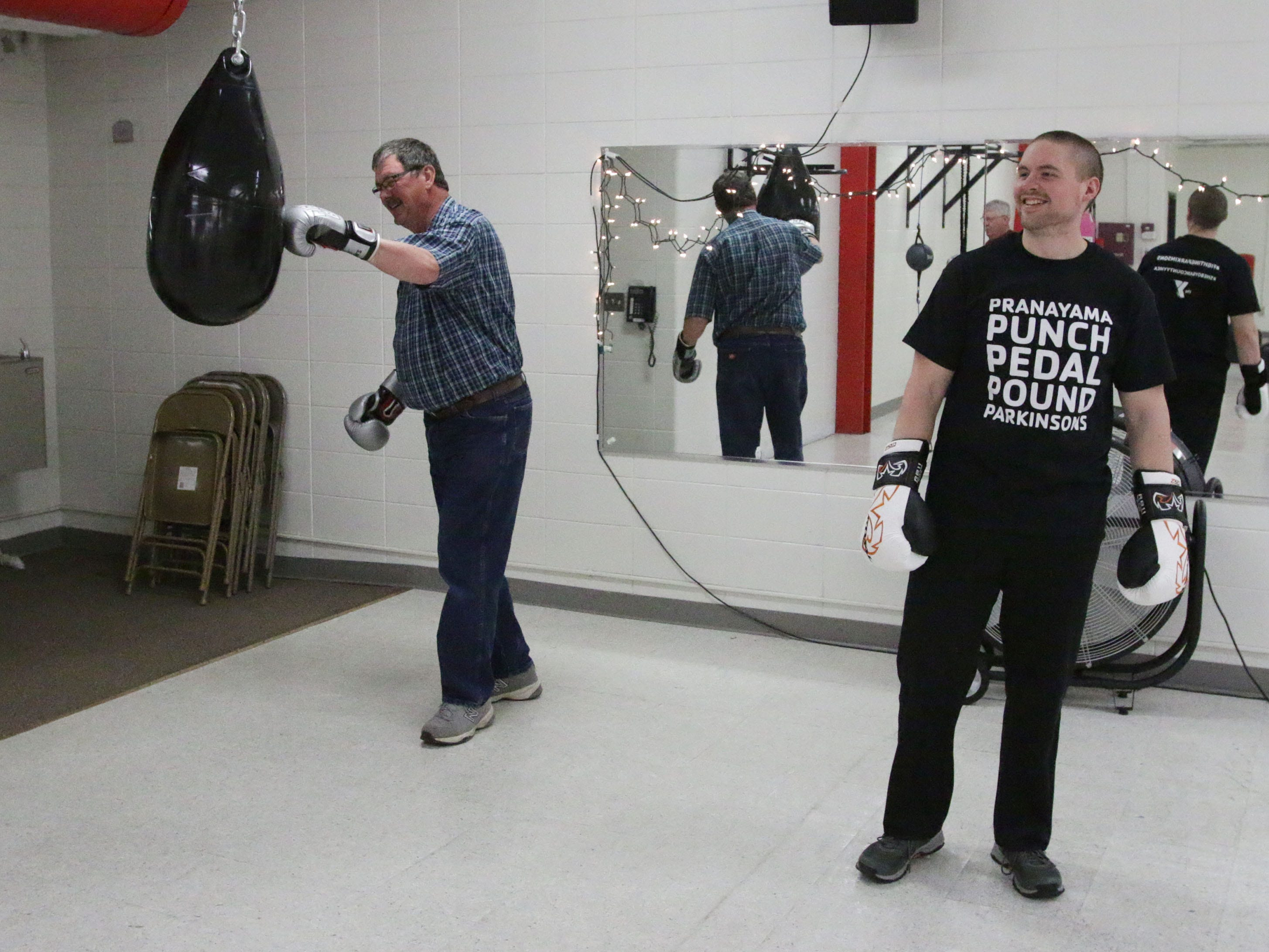 Greg Van Helden, of Sheboygan, left, hits the punching bag during the YMCA Fighting Parkinson's class near instructor Matt Glenzer, Tuesday, March 26, 2019, in Sheboygan, Wis.