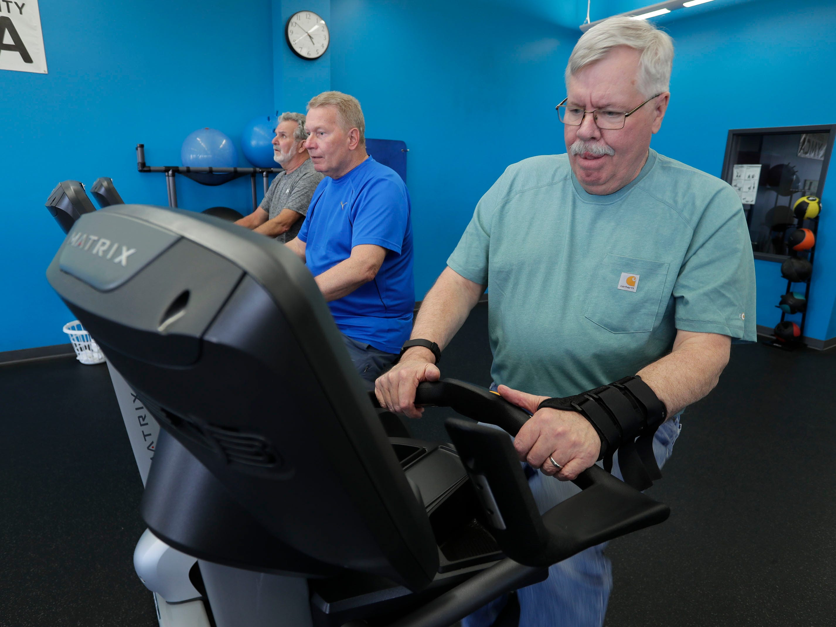 Larry Boll, left, Ken Pipping, center, and Ralph Worm, get in miles on stationary cycles during Fighting Parkinson's class at the YMCA Thursday, March 21, 2019, iin Sheboygan, Wis.