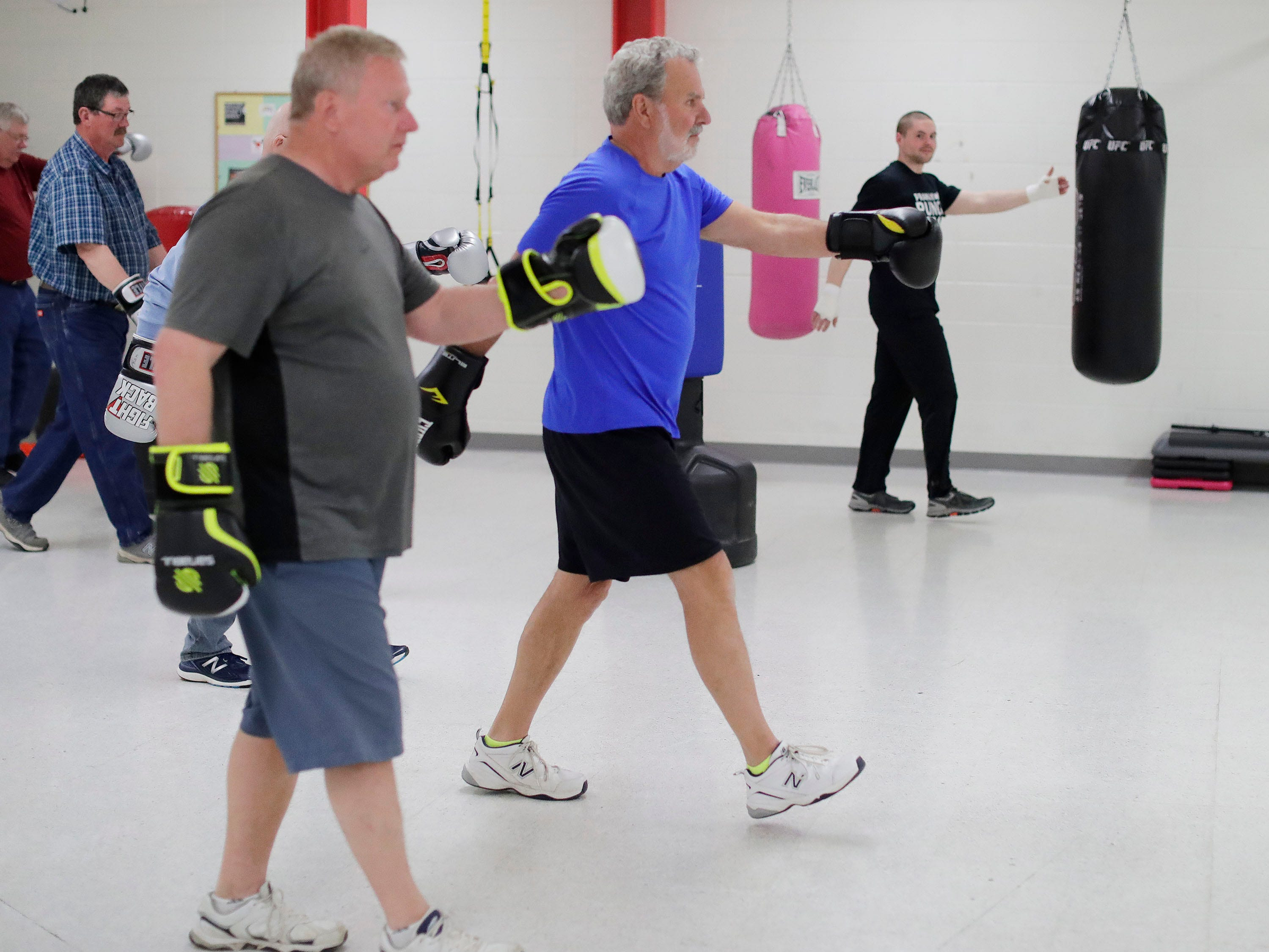 Students in the Fighting Parkinson's class take in a step routine to improve their motor function during a workout at the YMCA with instructor Jana Adams, right, Tuesday, Mach 26, 2019, in Sheboygan, Wis.