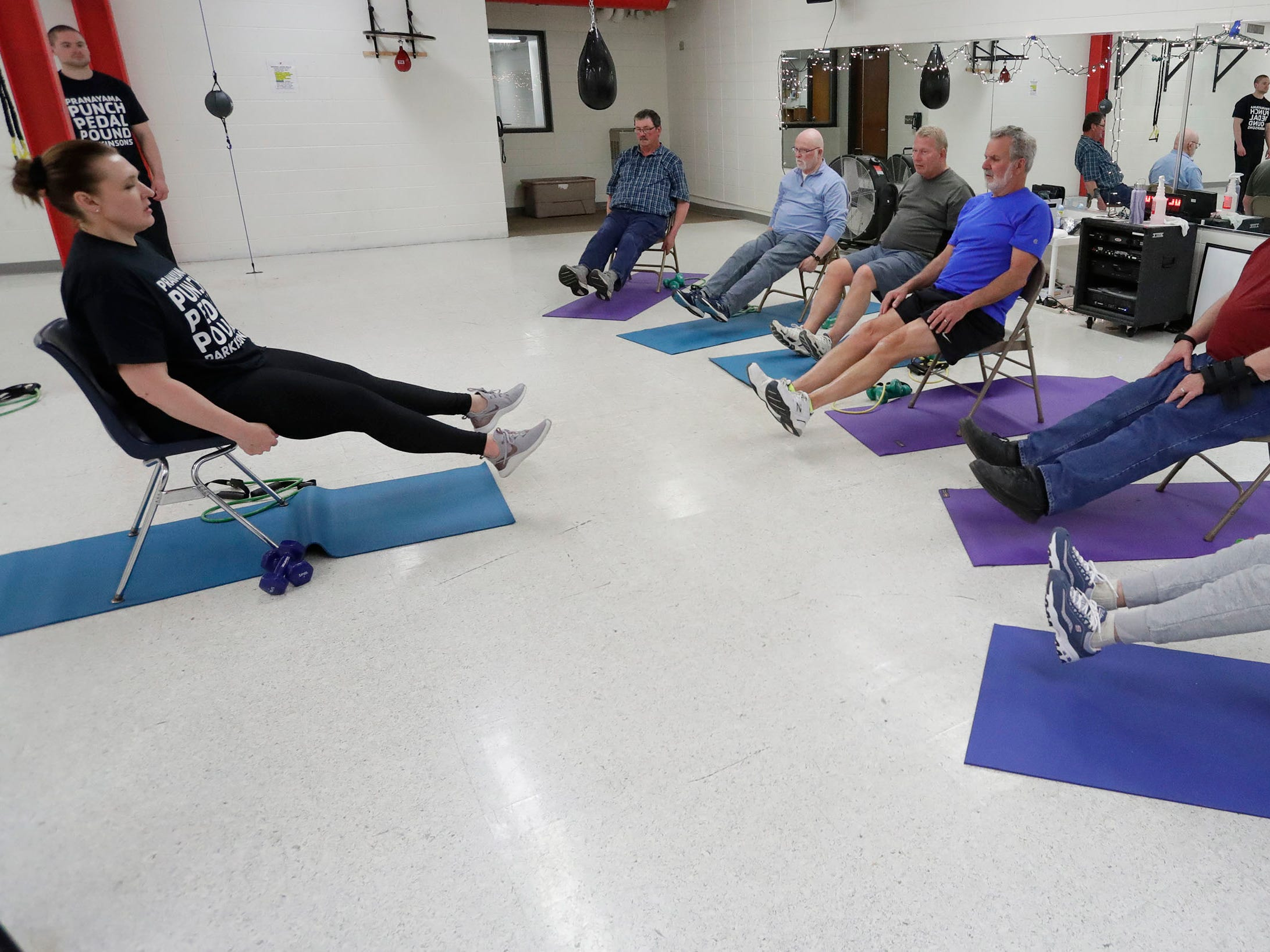 Instructor Jana Adams, left, works her Fighting Parkinson's class with leg lifts at the YMCA, Tuesday, March 21, 2019, in Sheboygan, Wis.