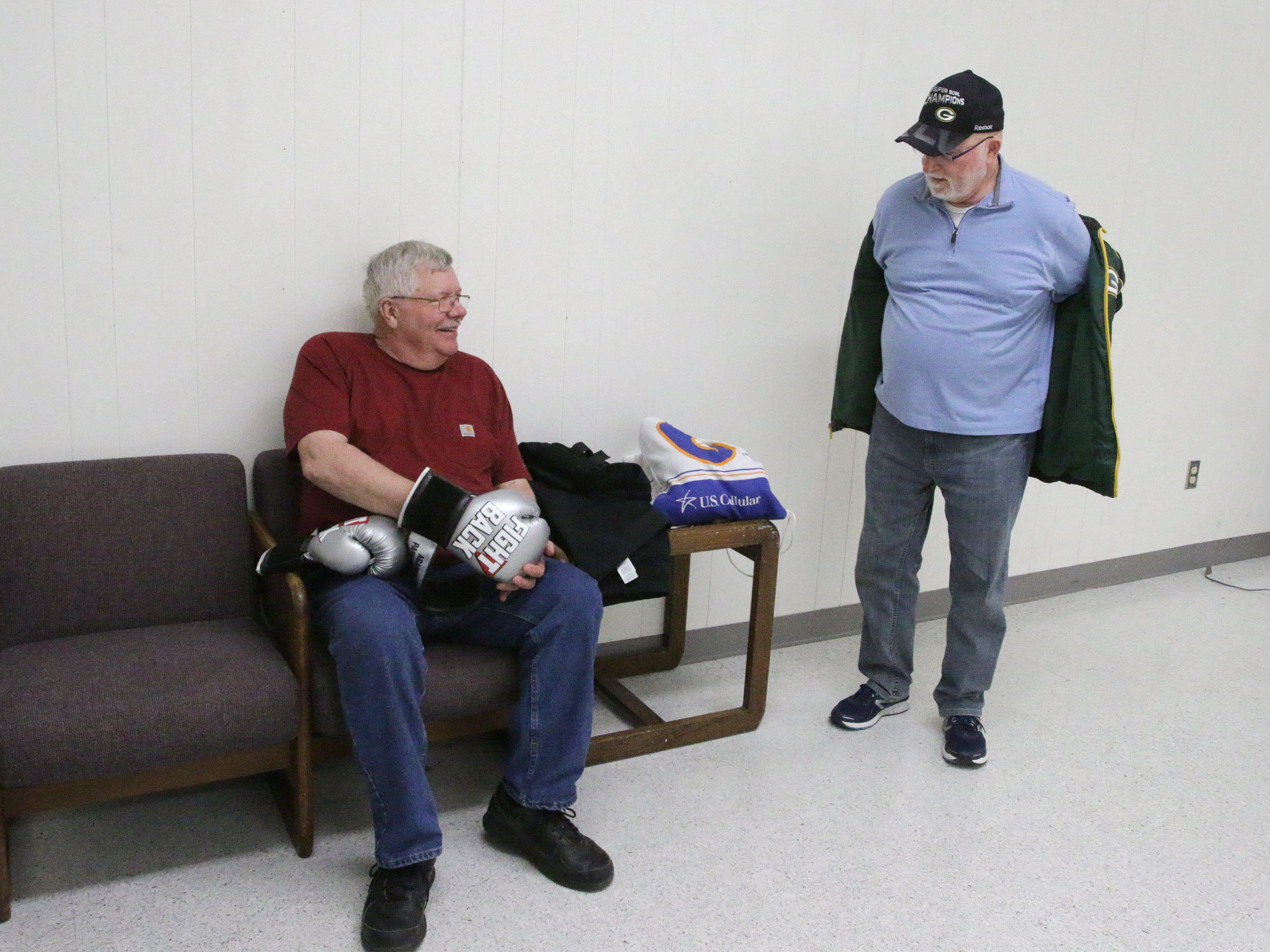 Ralph Worm of Sheboygan, left, shares a light moment before the YMCA Fighting Parkinson's class with Ken Pipping of Elkhart Lake, Tuesday, March 26, 2019, in Sheboygan, Wis.
