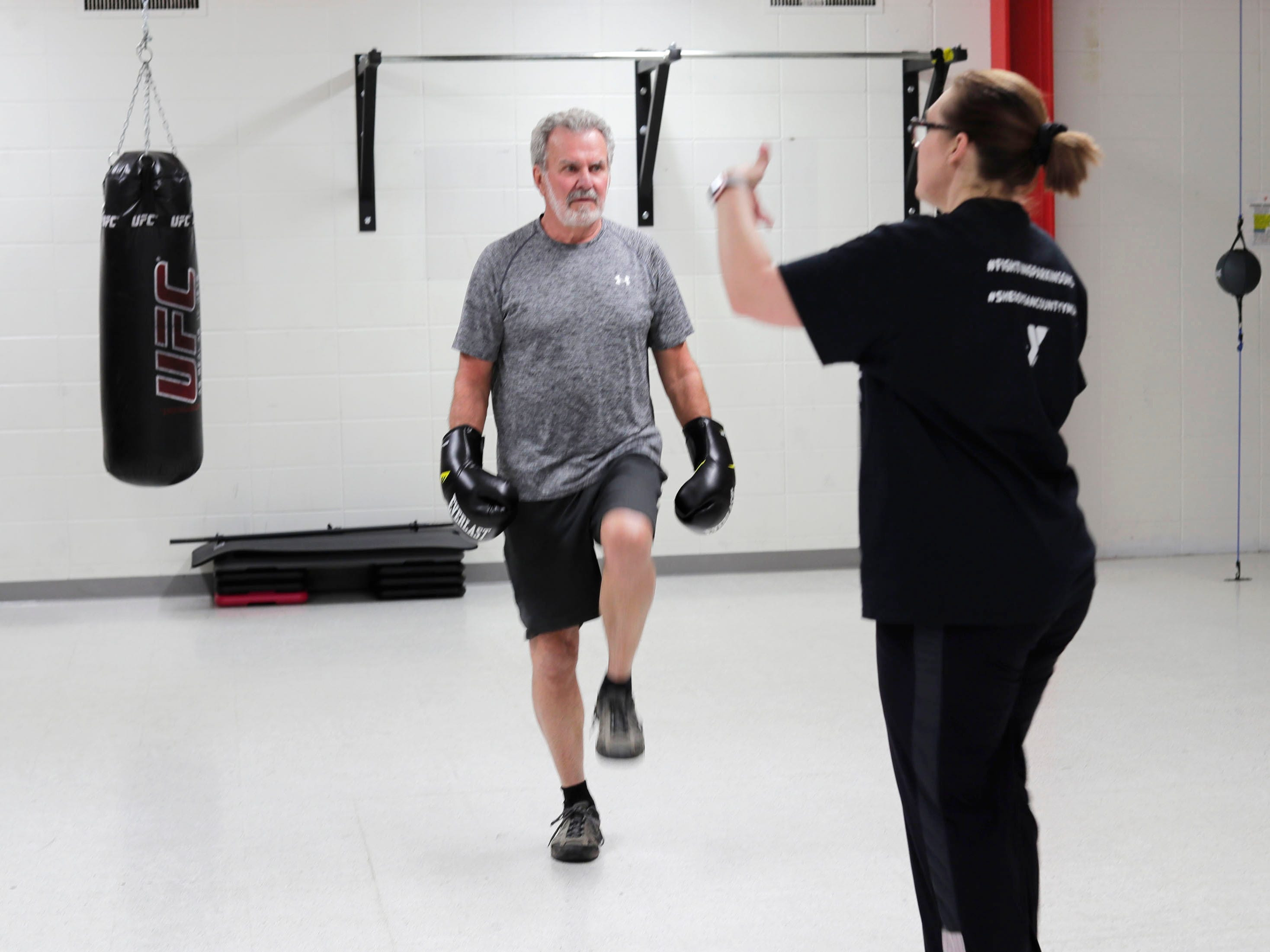 Larry Boll of Sheboygan, left, balances on one foot during the Fighting Parkinson's class at the YMCA while instructor Jana Adams gives him advice during the class, Thursday, March 21, 2019, in Sheboygan, Wis.