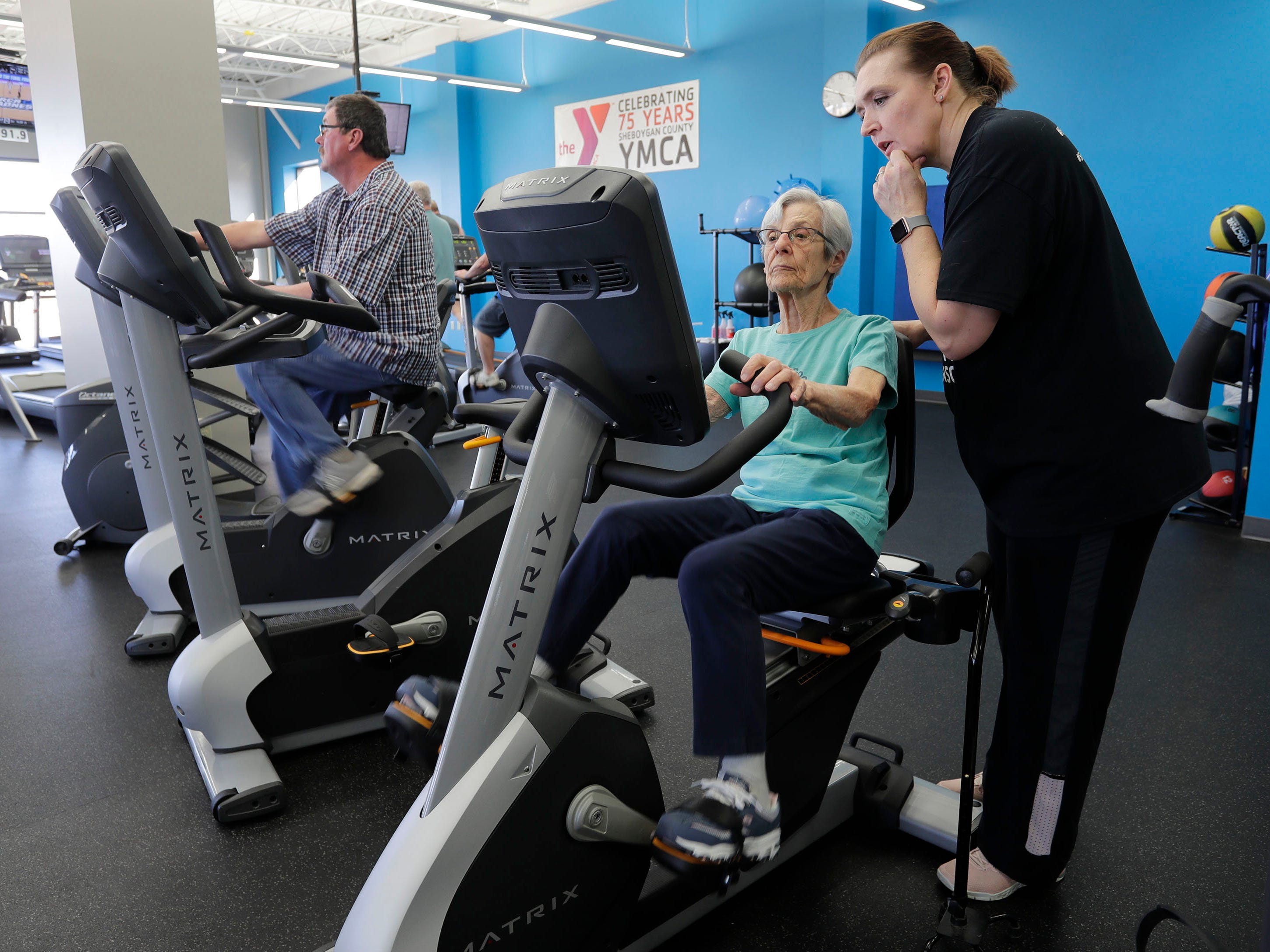Fighting Parkinson's instructor Jana Adams, right consults Darle Kosup, center, with tips to make her stationary bike training work for helping her battle during the class at the YMCA, Thursday March 21, 2019, in Sheboygan, Wis.