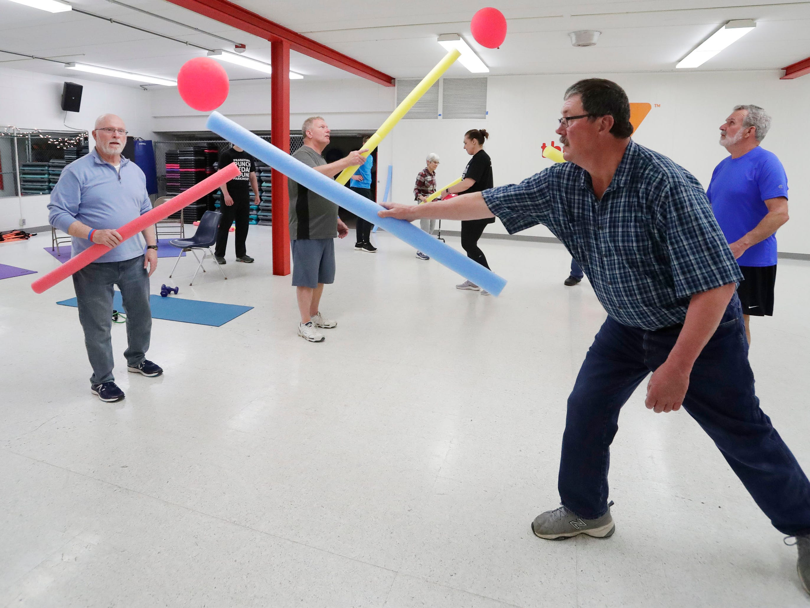 Ken Pipping of Elkhart Lake, Wis., left, waits for the balloon from Greg Van Helden of Sheboygan, during a YMCA Fighting Parkinson's class, Tuesday, March 21, 2019, in Sheboygan, Wis.