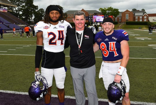 Northwestern State head coach Brad Laird (middle) poses with the MVPs of the Joe Delaney Bowl, Ian Edwards (24) and Gavin Landry.