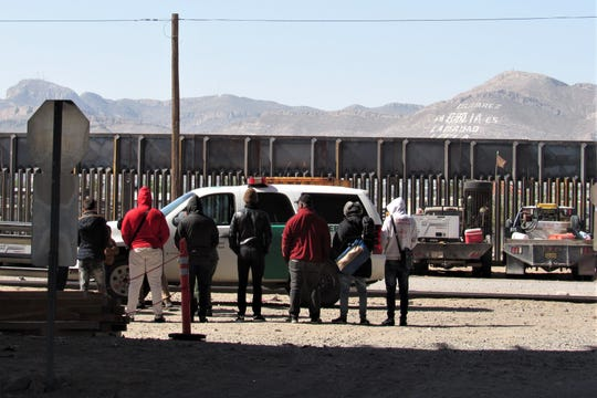 People stand by a Border Patrol SUV near the newly built section of the border wall near the Chihuahuita neighborhood of El Paso on Sunday, March 31, 2019. They later were taken away in a Border Patrol van.