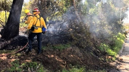 Firefighters battle a blaze Saturday alongside Highway 101 and the railroad tracks in Santa Barbara.