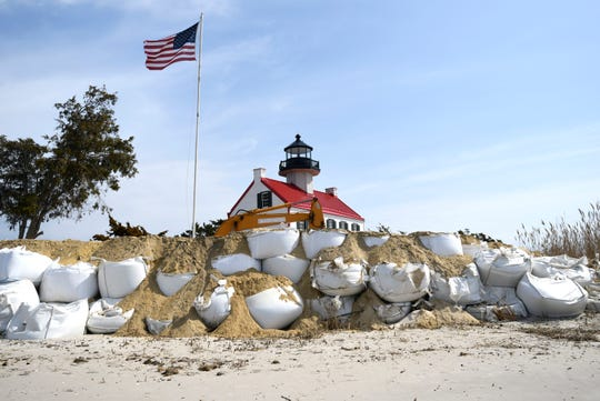 Crews work to bury bags of sand in front of East Point Lighthouse which will help reinforce the dunes lost to recent storms and rising sea levels.