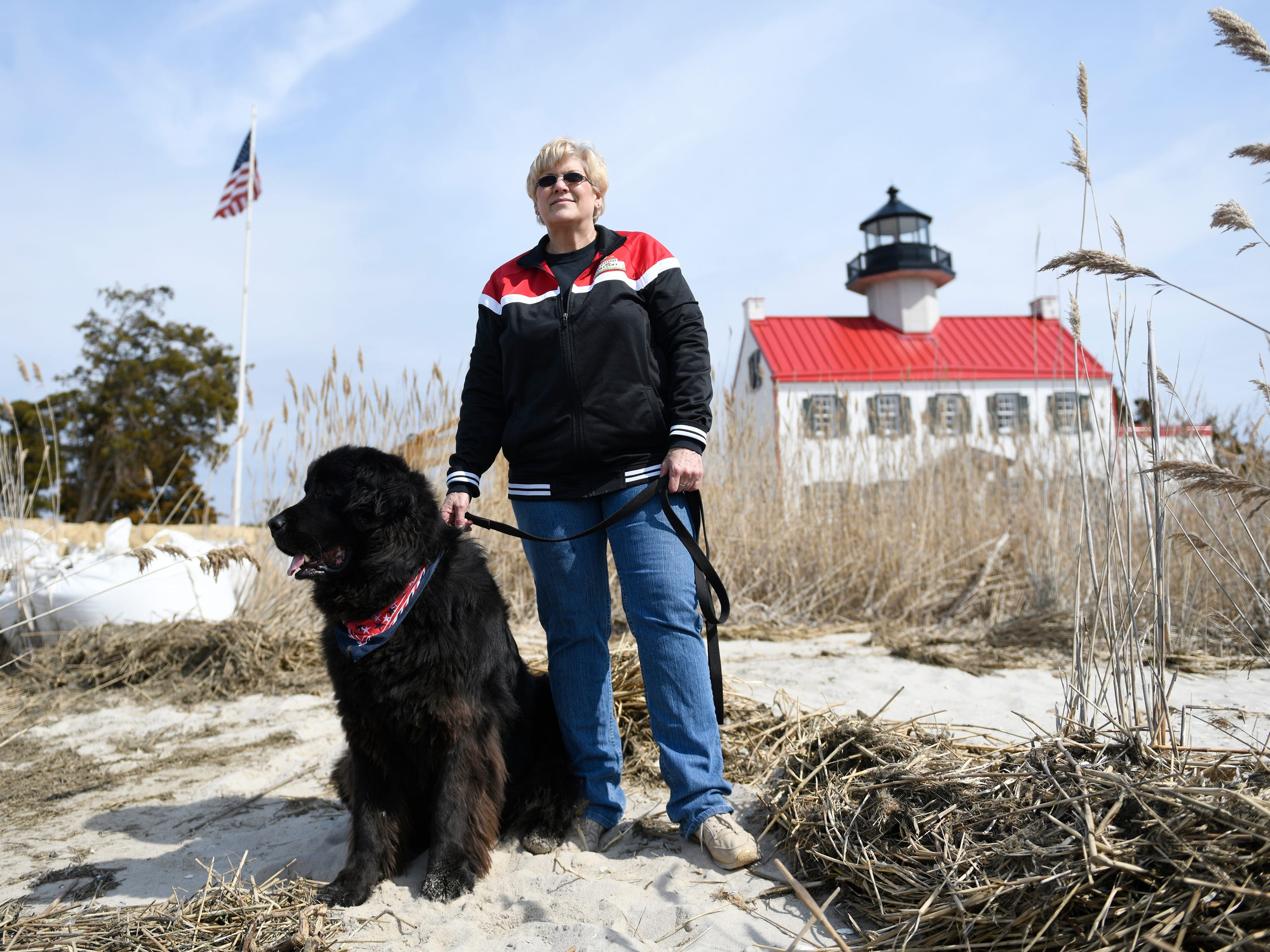 Nancy Patterson, manager of the East Point Lighthouse in Cumberland County looks out into the Delaware Bay with her dog Captain.