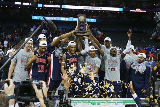 Auburn players celebrate with the Midwest Regional trophy after defeating  Kentucky to advance to their first Final Four.