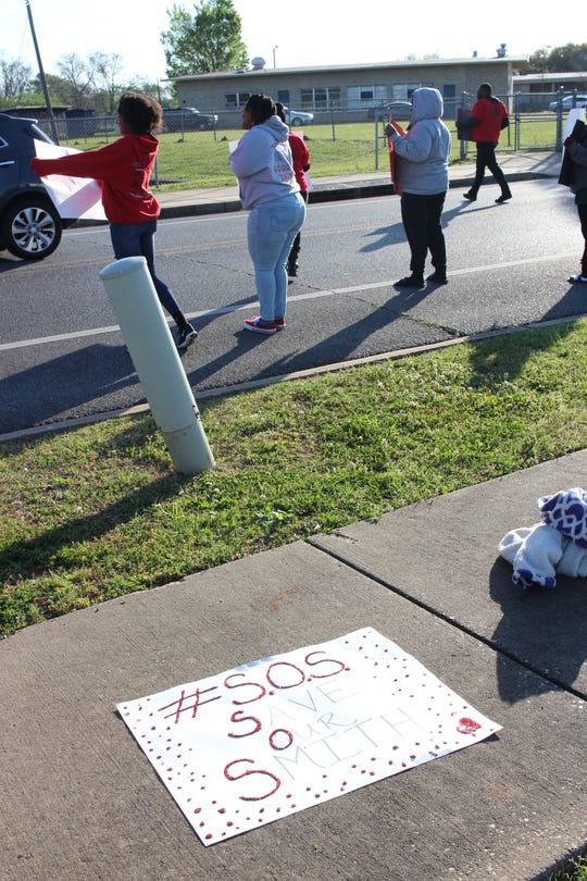 "A sign that reads ""S.O.S. Save Our Smith"" lies on a sidewalk Monday morning. Supporters of Arthur F. Smith Middle Magnet School, teachers and parents, were protesting an option to close the 58-year-old school that Rapides Parish School Board members could consider during its Tuesday meeting."