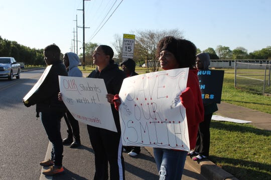 Protesters seek support from drivers on Monday morning outside Arthur F. Smith Middle Magnet School. The Rapides Parish School Board could consider an option to close the school during its meeting Tuesday.