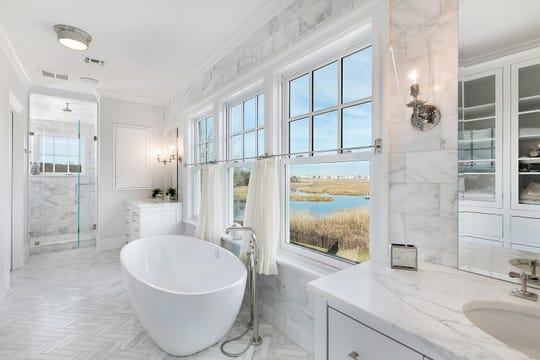 The Master bath features custom windows, marble tile flooring and sinks.