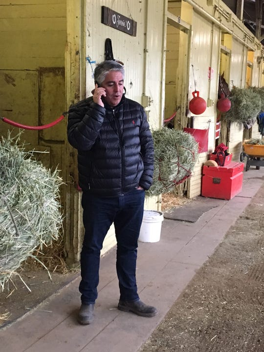 Trainer Gregg Sacco talks on the phone in his barn at Belmont Park last week