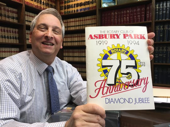 Sandy Brown, Rotary Club of Asbury Park historian, holds up the club's 75th anniversary program from 1994.