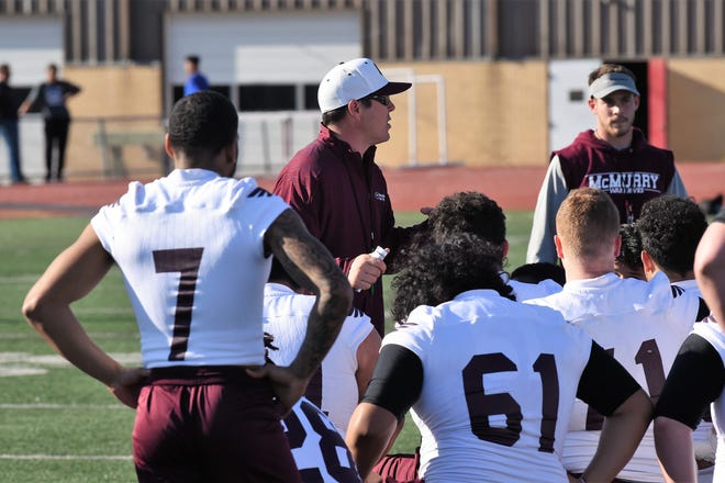 McMurry University football coach Jordan Neal talks to the War Hawks after their first spring practice at Wilford Moore Stadium on Monday.