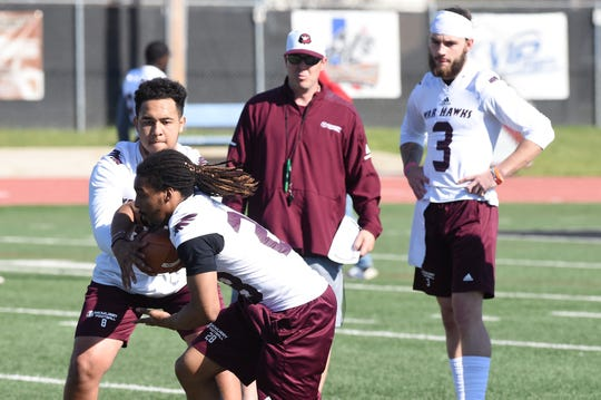 McMurry quarterback Matt Heifner (8) hands the ball off to Malik Collins (28) while coach Jordan Neal and quarterback Kevin Hurley Jr. (3) look on during the first spring practice at Wilford Moore Stadium on Monday, April 1, 2019.