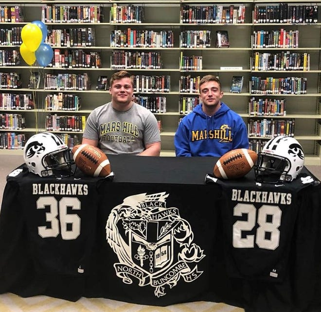 Skylar Jutras (28) and Eric Rice (36) signed to play college football at Mars Hill University on March 29, 2019.