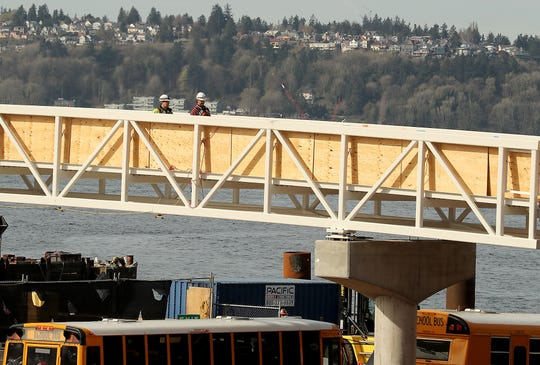 Construction workers move along the elevated walkway that connects the main ferry terminal building with the passenger-only ferry facility at Colman Dock in Seattle on Monday.