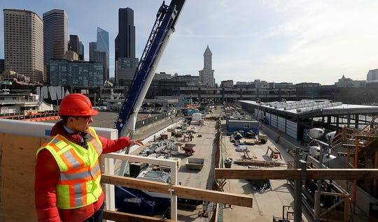 WSF spokesperson Broch Bender points out the different aspects of the passenger-only ferry facility (at right) and the ferry vehicle traffic lanes that are both still under construction at Colman Dock in Seattle on Monday.