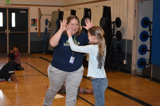 Sand Hill Elementary PE teacher Nicole Funk cheers on a student after a jump rope test.