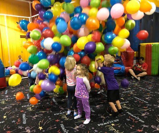 Isabella seems oblivious to the fact that hundreds of balloons are falling behind her.
