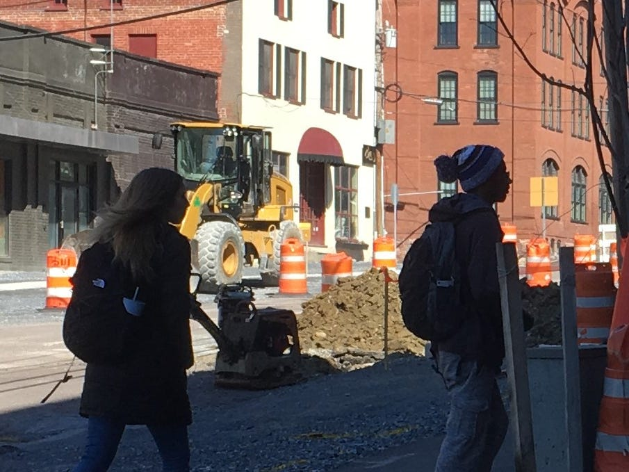 Champlain College students walk along the eastern side of St. Paul Street in Burlington while road construction resumes on April 1, 2019.