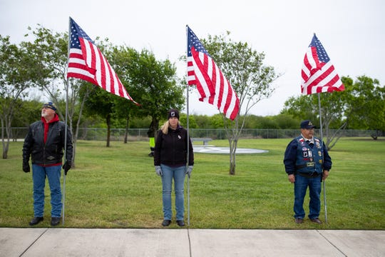 Veterans hold American flags during the military burial of United States Air Force SGT Andrew Cavazos Ybarra at the Coastal Bend State Veterans Cemetery on Monday, April 1, 2019.