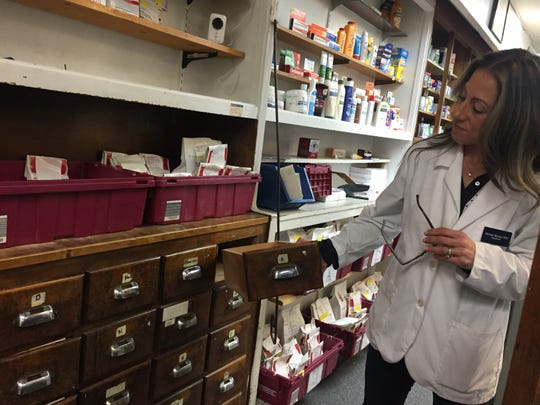 Marian Morton shows a pharmacist's cabinet, one of the older fixtures at Bell Pharmacy.