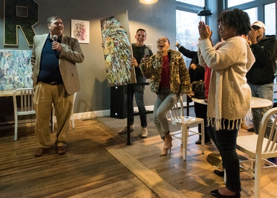 Attendees at Another Chance Ministry's Night of Hope rejoice after John Ward, left, auctions a painting from Alec Wiggin (not pictured) Sunday night to benefit the ministry which provides faith-based transitional housing for men in recovery. Wiggin began painting while in the Another Chance program.