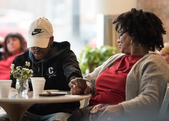 Joshua Howard, left, holds his mother Sarina Vinson's hand as they listen to testimonials from those who have struggled with drug addiction and how their lives have changed during and after their addictions.