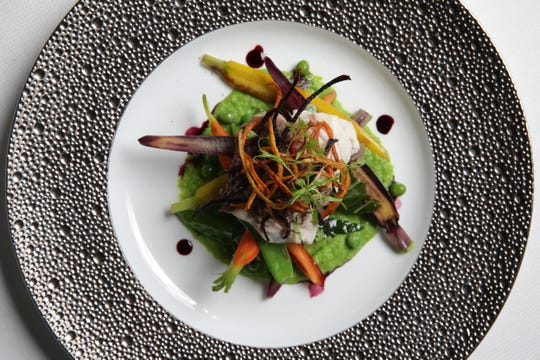 Red snapper with a medley of spring vegetables and pea puree with a pinot noir reduction, pictured, Friday, March 29, 2019, at Restaurant L at Queen City Square in Cincinnati.