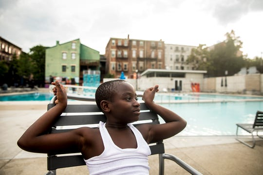 Miron Siler sits by the pool for his swim team's end of the season party at Ziegler Pool in Over-the-Rhine Wednesday, August 1, 2018