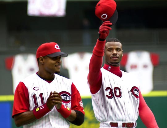 Ken Griffey Jr. salutes the crowd with Barry Larkin as he takes the field for the first introduction as a Cincinnati Red at Cinergy Field on April 3, 2000.