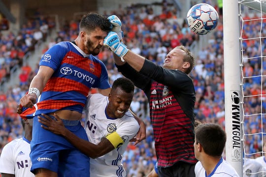 First place, Sports Action - FC Cincinnati defender Forrest Lasso (3) is punched in the face by Charlotte Independence goalkeeper Andrew Dykstra (50) on an attempt on goal in the first half of a USL match, Wednesday, July 18, 2018, at Nippert Stadium in Cincinnati. FC Cincinnati leads 2-0 at halftime.