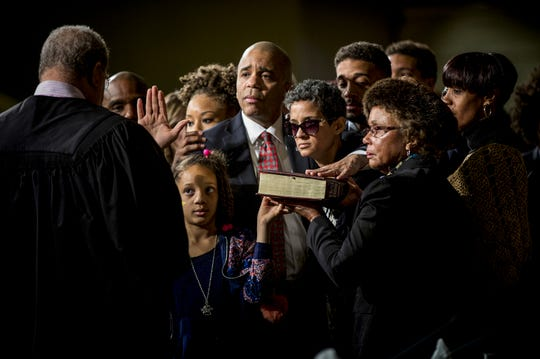 First place, General News - Council Member Christopher Smitherman is sworn in as vice mayor while surrounded by his family at the inaugural session of the city council held at the Music Hall ballroom Tuesday, January 2, 2018. Smitherman's wife, Pamela, is battling breast cancer and was not expected to live to her husband's swearing in ceremony. Her family supports her to stand by her husband.