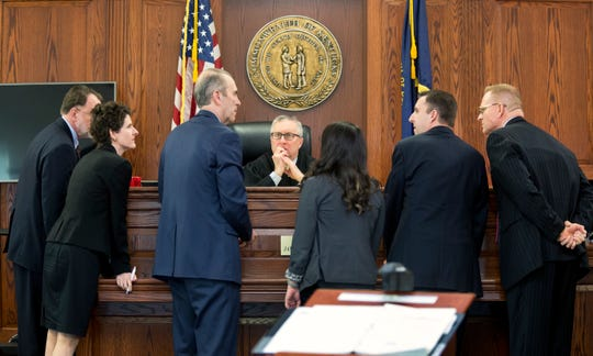 Boone County Circuit Court Judge James R. Schrand talks with lawyers Monday, April 1, 2019, during a hearing on the whether public health officials were within their rights to keep Jerome Kunkel, 18, a senior at Assumption Academy in Walton, Kentucky, from attending classes or playing basketball after an outbreak of chicken pox. Kunkel has never been vaccinated due to a religious exemption.