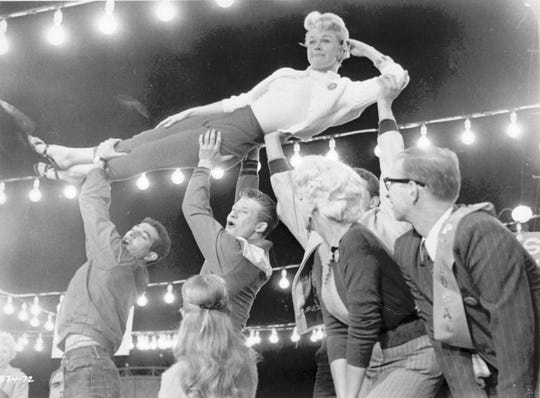"Cincinnati native Doris Day is hoisted aloft during the ""Seven and a Half Cents"" number from the 1957 movie of the Broadway musical, ""The Pajama Game."""