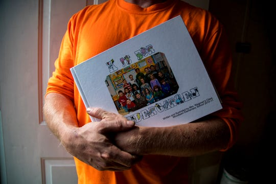 Michael Chase holds his daughter's kindergarten yearbook at his home in Montgomery County on March 14, 2019. Chase lost his daughter, Ariel, to suicide on March 4, 2019.