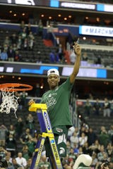 MSU's Cassius Winston cuts down the net after MSU's 68-67 win in the NCAA tournament East Region final on Sunday, March 31, 2019, in Washington.