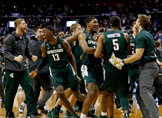 Michigan State celebrates after beating Duke in the NCAA tournament East Region final on Sunday, March 31, 2019, in Washington.