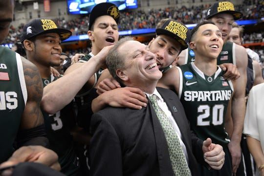 MSU head coach Tom Izzo gets a hug from player Denzel Valentine, center, with players Alvin Ellis, Gavin Schilling, Travis Trice, and Matt Costello left to right behind, after MSU's 76-70 win over Louisville in their NCAA Elite Eight  game in Syracuse, NY Sunday 3/29/2015.