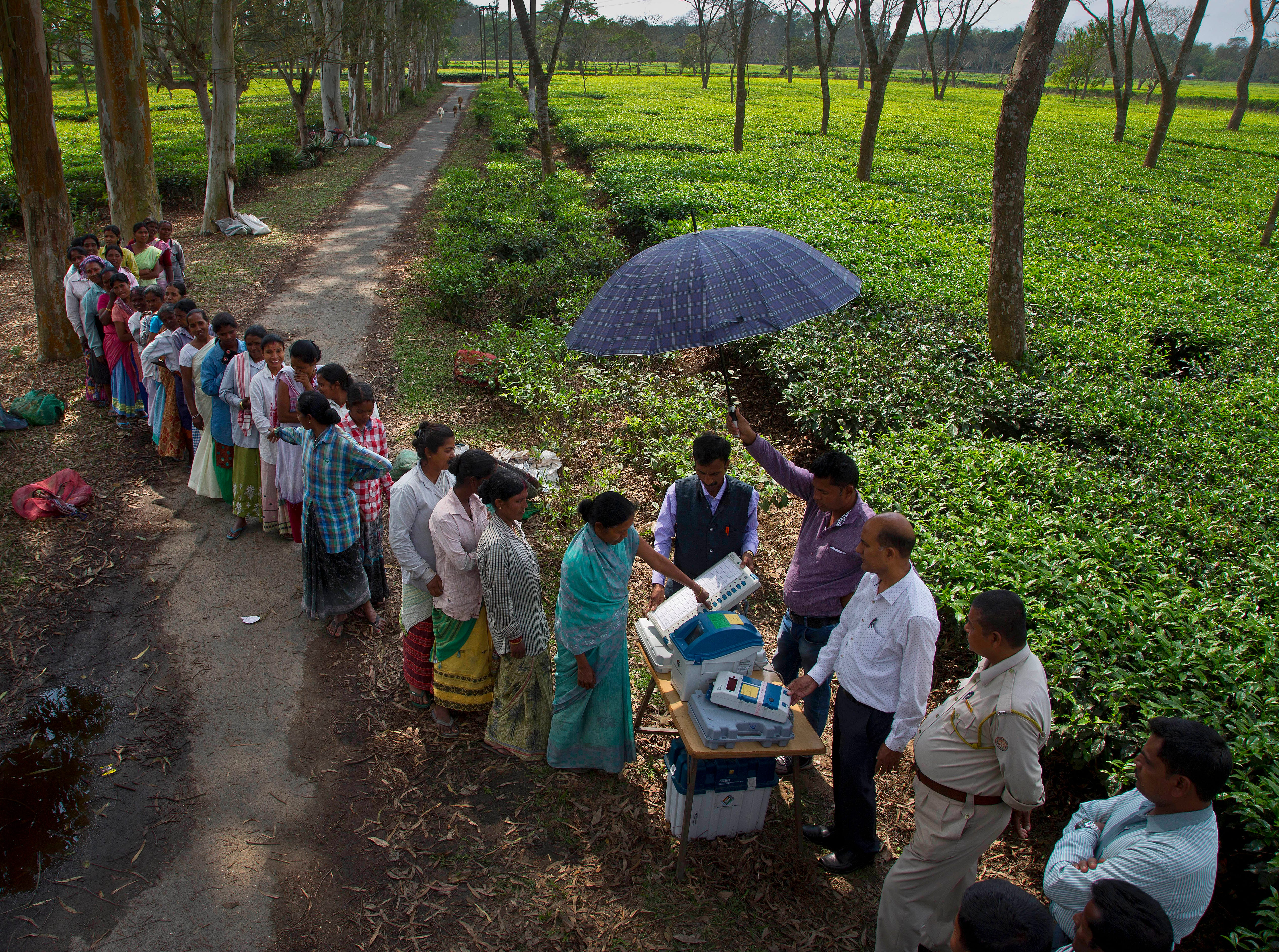 A woman casts her vote on the demo electronic voting machines and checks on Voter Verifiable Paper Audit Trail or VVPAT as others wait in the queue during an election awareness drive by district administration amongst the tea garden laborers ahead of India's general election in Jorhat, India, Monday, April 1, 2019. A VVPAT vending machine is an independent printing system connected to the electronic voting machines that allows voters to check that their votes are being cast as intended. The system will be used in the upcoming national elections to be held in seven phases starting from April 11. Votes will be counted on May 23.