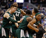 Michigan State guard Cassius Winston, right, celebrates with teammates Matt McQuaid (20), Nick Ward (44) and Gabe Brown (13) after defeating Duke in an NCAA men's East Region final Sunday.