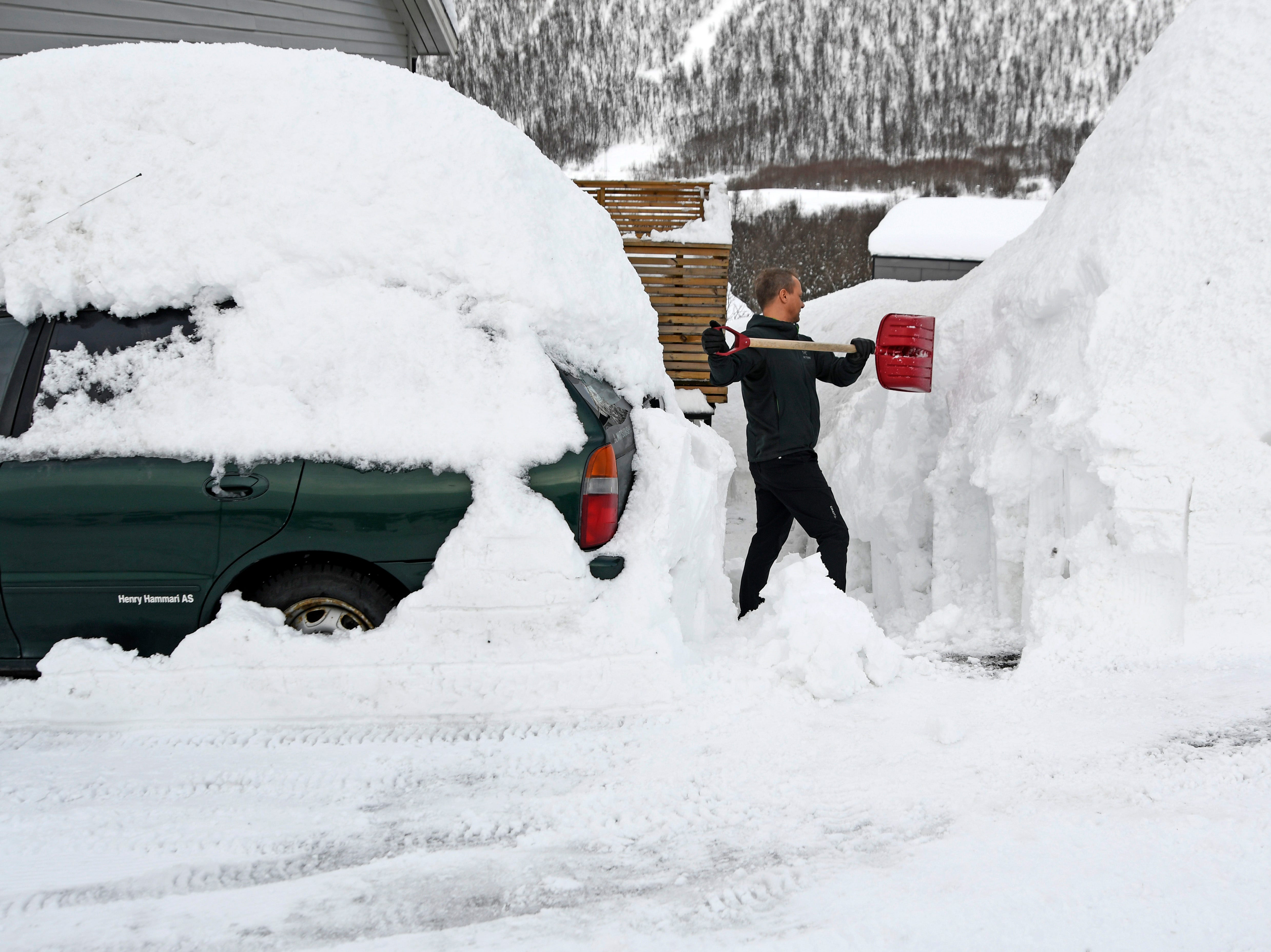 Hans Otto Larsen shovels snow in front of his house in Tromso, Norway, Monday April 1, 2019. Huge amounts of snow have created chaos in the northern parts of Norway.