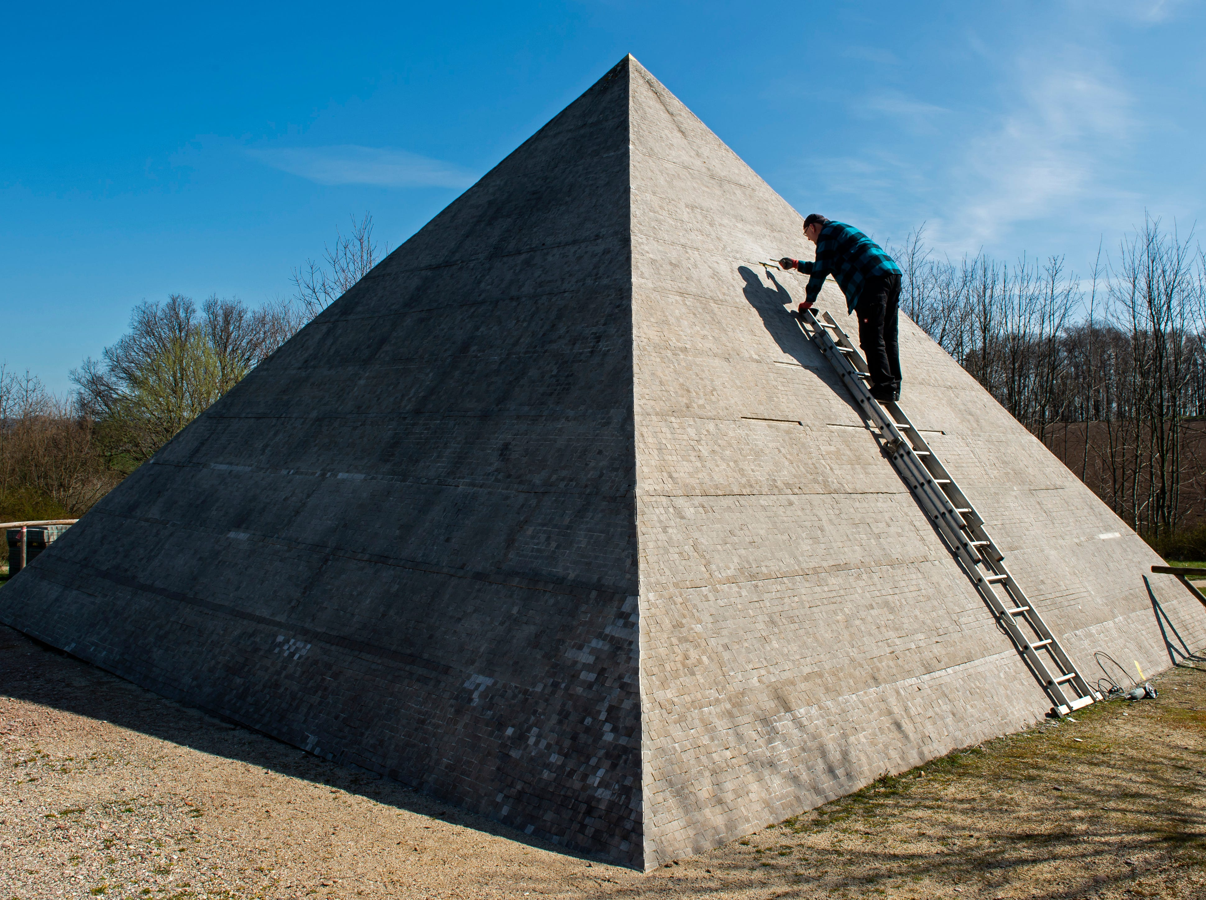 A worker fixes small stones at the model of the Cheops pyramid of Giza during the annual renovation prior the season's opening next weekend in the landscape park Miniwelt (Miniworld) in Lichtenstein, eastern Germany, Monday, April 1, 2019. The cultural park Miniworld presents about 100 original and true-to detail buildings and technical facilities at a 1:25 scale ranging on an area of 6,5 hectare.